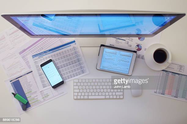 overhead view of desk space with financial documents - financial technology stock photos and pictures