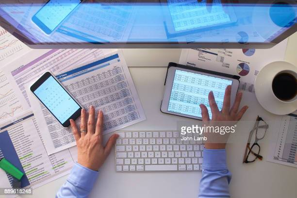 overhead view of desk space with hands - financial technology bildbanksfoton och bilder