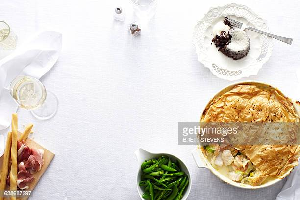 Overhead view of dinner table with chicken and leek pie, green beans and chocolate pudding dessert