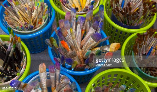 overhead view of dozens of old paintbrushes in containers - tempera painting stock pictures, royalty-free photos & images
