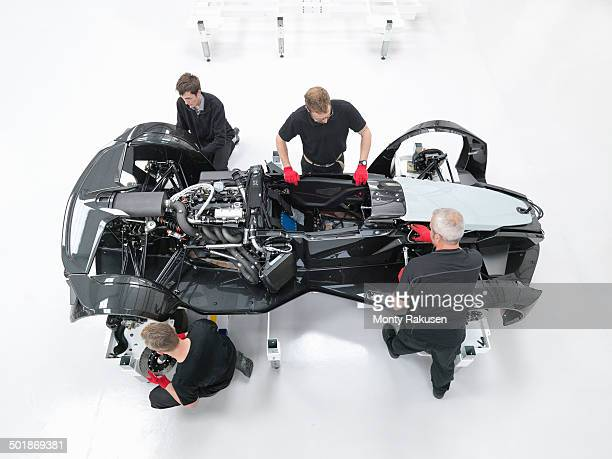 Overhead view of engineers assembling supercar in sports car factory