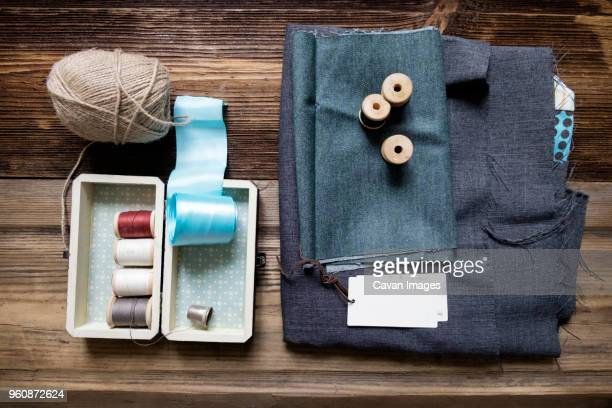 overhead view of fabric with sewing equipment on wooden table - ribbon sewing item stock pictures, royalty-free photos & images