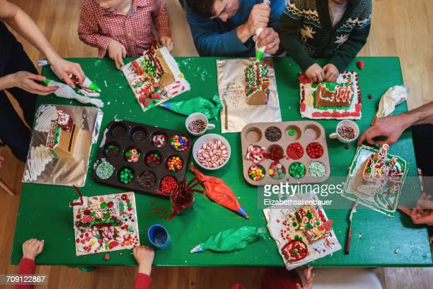 Overhead view of family decorating gingerbread houses