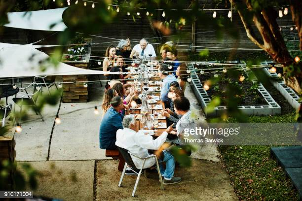 overhead view of family seated together on outdoor patio for celebration dinner - southern usa stock pictures, royalty-free photos & images