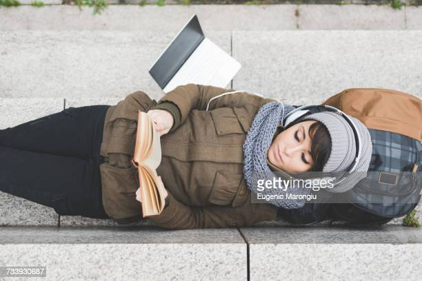 Overhead view of female backpacker lying on back reading book on wall