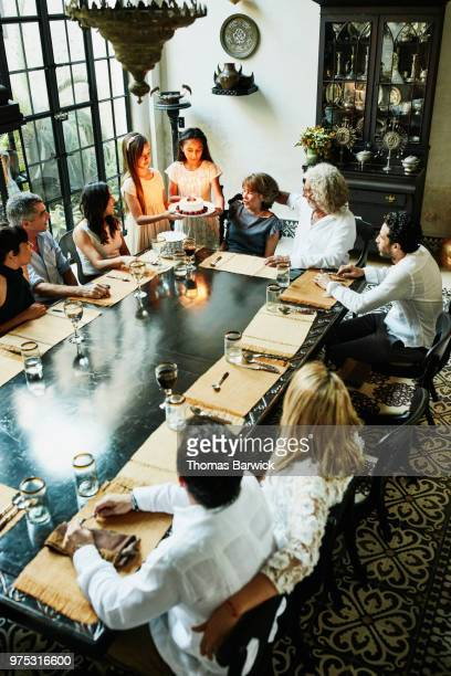 Overhead view of female cousins bringing birthday cake with candles to dinner table during family birthday party