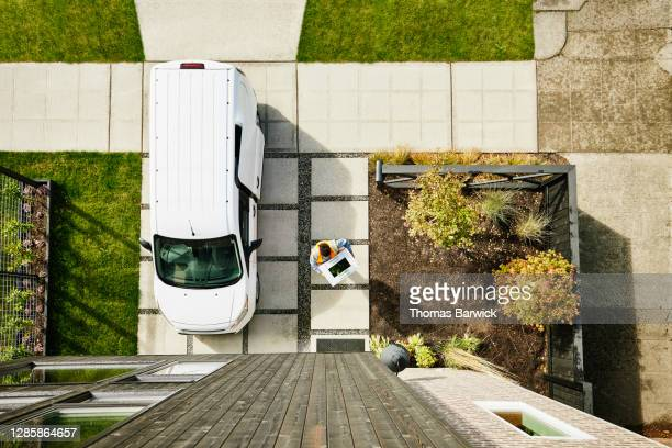 overhead view of female delivery driver carrying produce box to front door of home - returning merchandise stock pictures, royalty-free photos & images