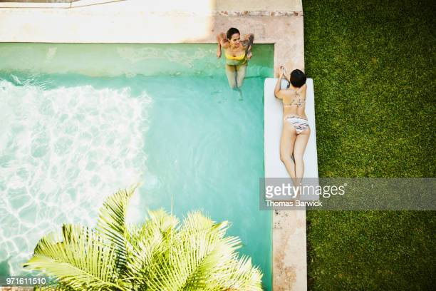 Overhead view of female friends in discussion while relaxing by pool at outdoor spa