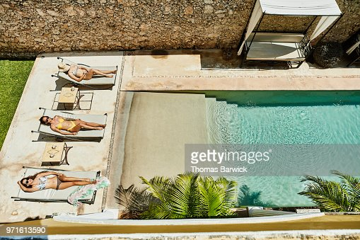 Overhead view of female friends relaxing in lounge chairs next to outdoor hotel pool
