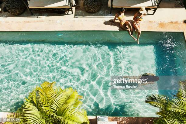 Overhead view of female friends seated next to outdoor hotel pool as friend swims underwater
