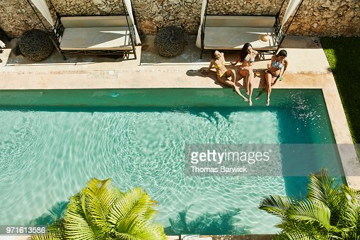Overhead view of female friends sitting next to outdoor hotel pool enjoying drinks