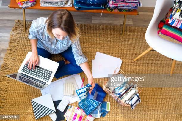 Overhead view of female interior designer using laptop on floor in retail studio