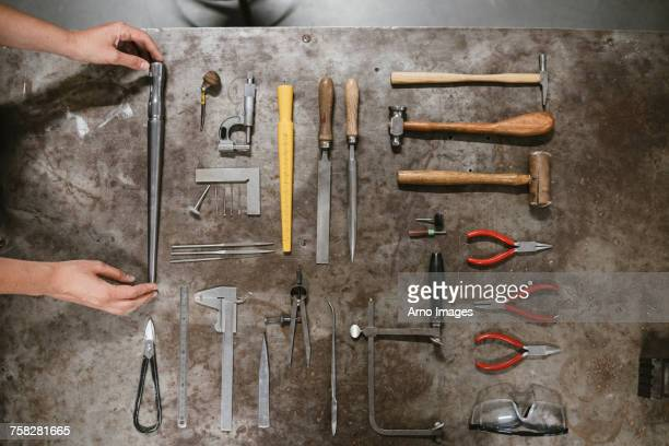 Overhead view of female jewellers hands laying out hand tools at workbench