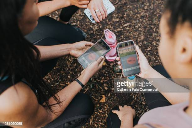 overhead view of female joggers looking at a fitness app on their smart phones - mobile app stock pictures, royalty-free photos & images