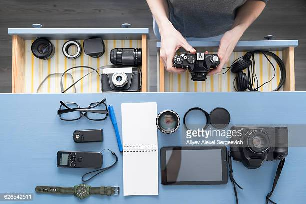 Overhead view of female photographers hands removing camera from desk drawer in studio