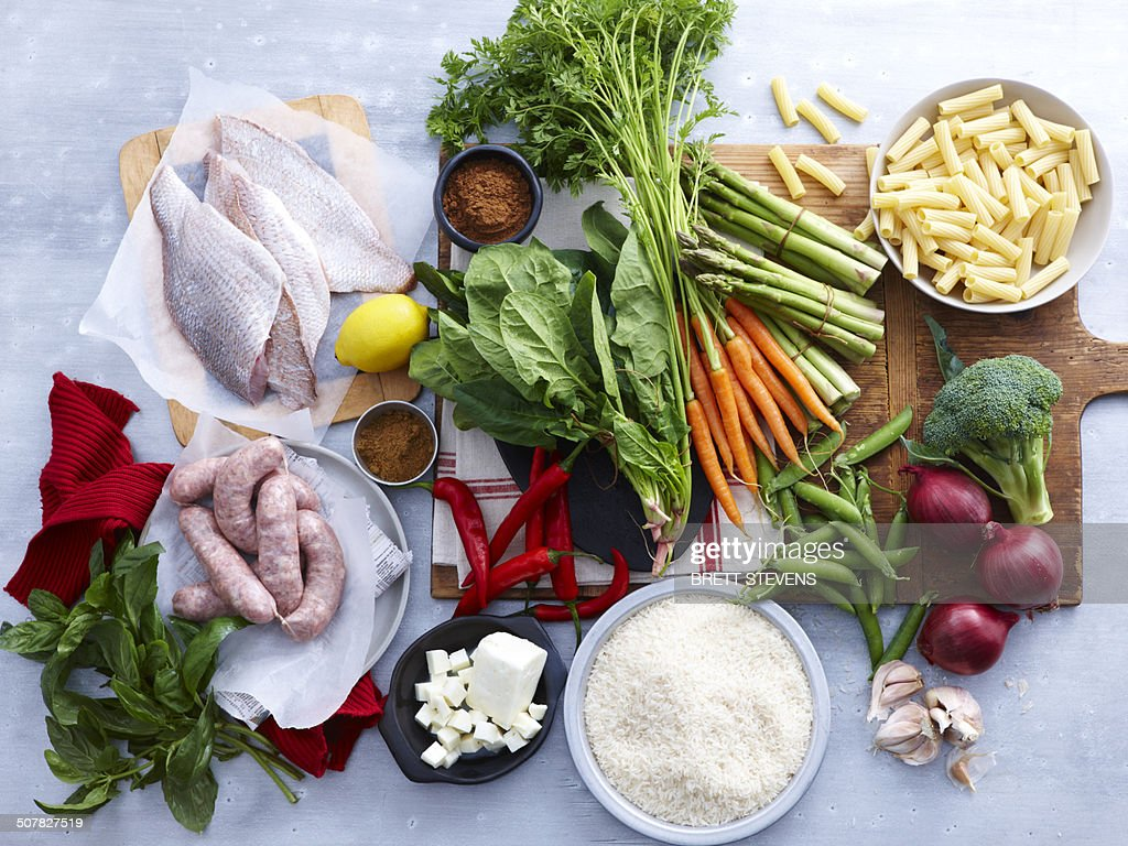 Overhead view of fish, pork sausage, feta and selection of fresh organic herbs and vegetable : Stock Photo