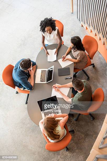 Overhead view of five business people at table in meeting