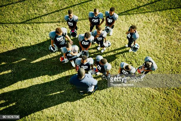 Overhead view of football coach talking to young players before football game