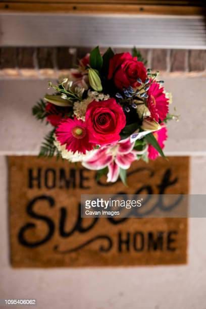 overhead view of fresh bouquet on retaining wall by doormat at entrance - home sweet home stock pictures, royalty-free photos & images
