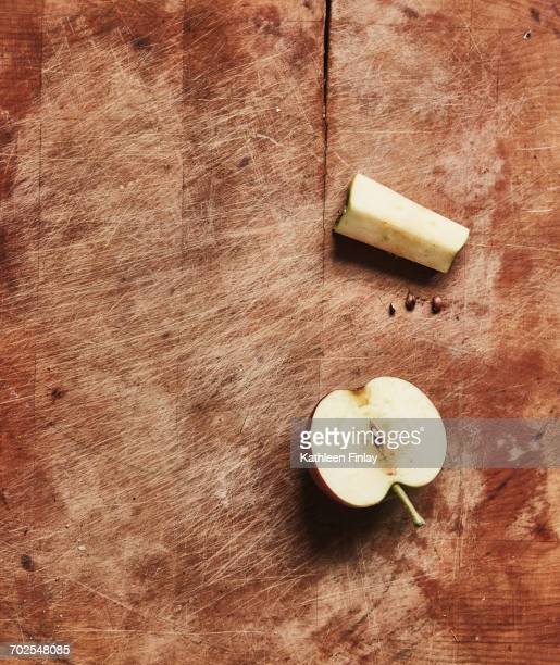 Overhead view of fresh halved apple and apple core on wooden cutting board