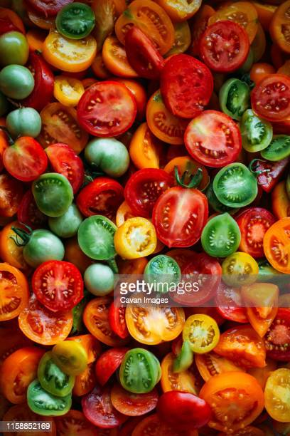 overhead view of fresh red tomatoes on table - harvest table stock pictures, royalty-free photos & images