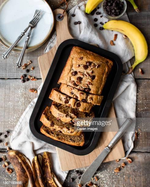 overhead view of freshly baked banana bread on wooden background. - banana loaf stockfoto's en -beelden