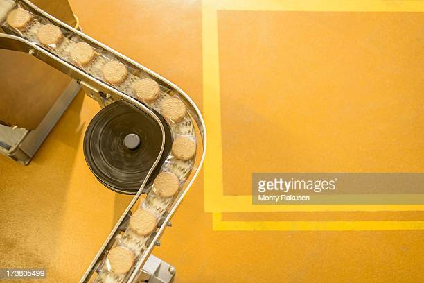 overhead view of freshly made biscuits on production line in food factory - same action stock photos and pictures