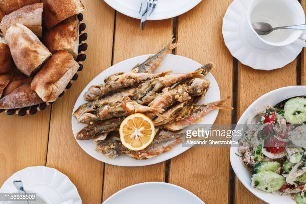 Overhead view of fried fish on wooden table