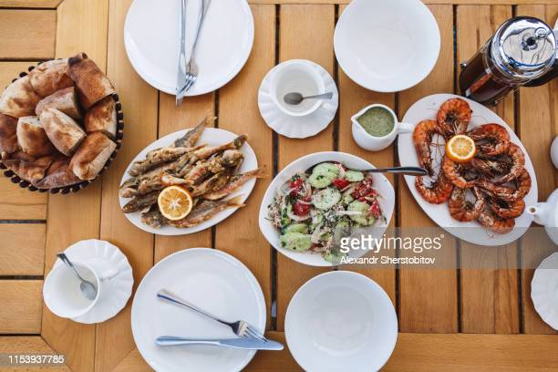 Overhead view of fried shrimps and fish on wooden table