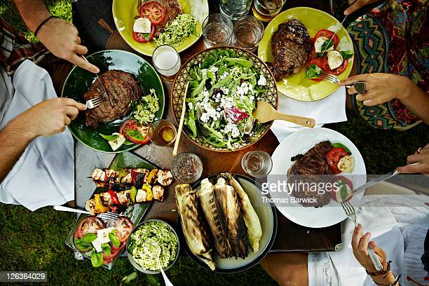 overhead view of friends dining at table outdoors - menselijk lichaamsdeel stockfoto's en -beelden