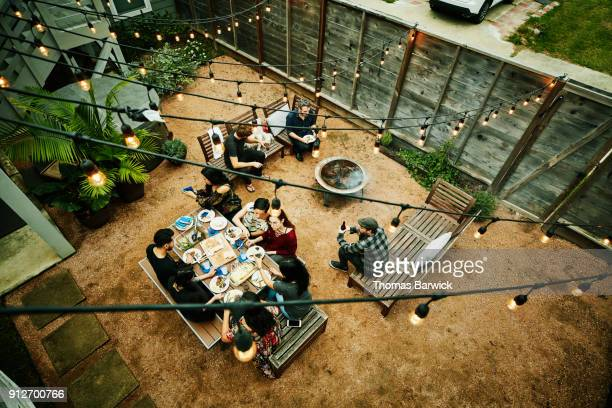 overhead view of friends dining during backyard barbecue - barbecue social gathering stock pictures, royalty-free photos & images