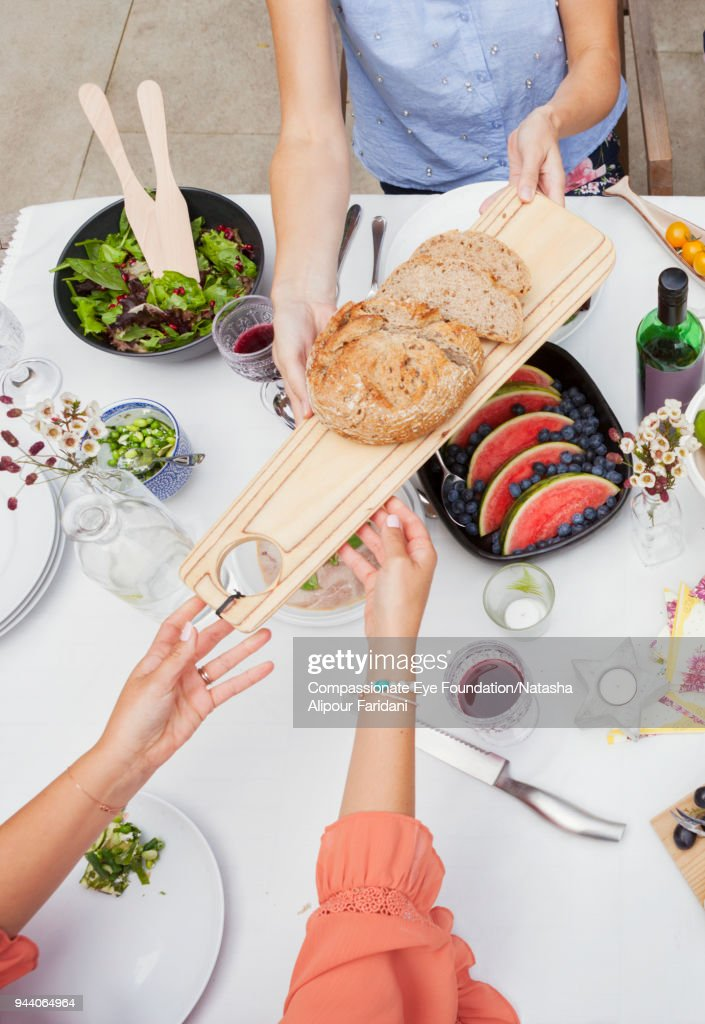 Overhead view of friends enjoying garden party lunch on patio table : Stock Photo