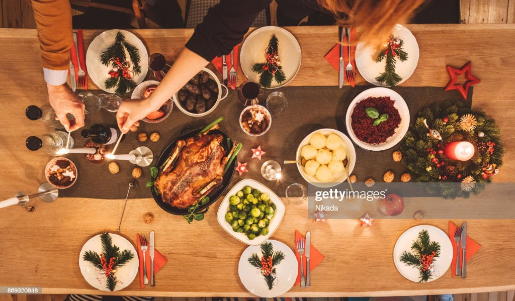 Overhead view of friends prepare table for christmas party : Stock Photo