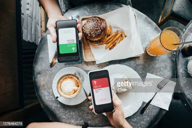 overhead view of friends sending/receiving the payment of the meal through digital wallet device on smartphone while dining together in a restaurant - exchanging stock pictures, royalty-free photos & images