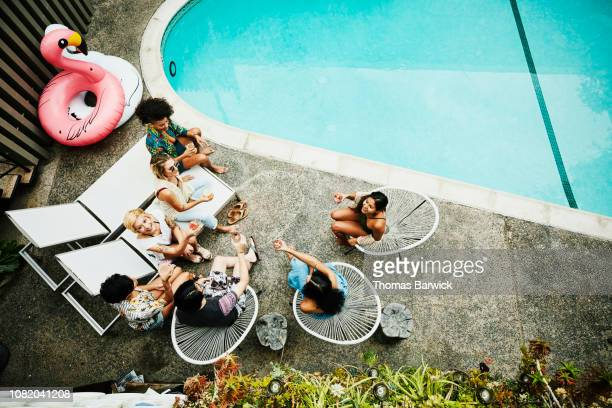 overhead view of friends sharing drinks while sitting beside hotel pool - pool party fotografías e imágenes de stock