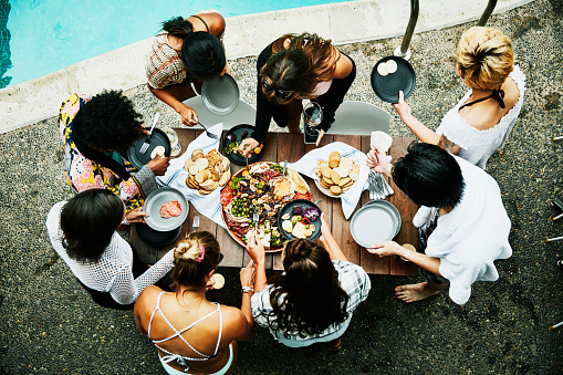 Overhead view of friends sharing food during pool party at hotel - gettyimageskorea