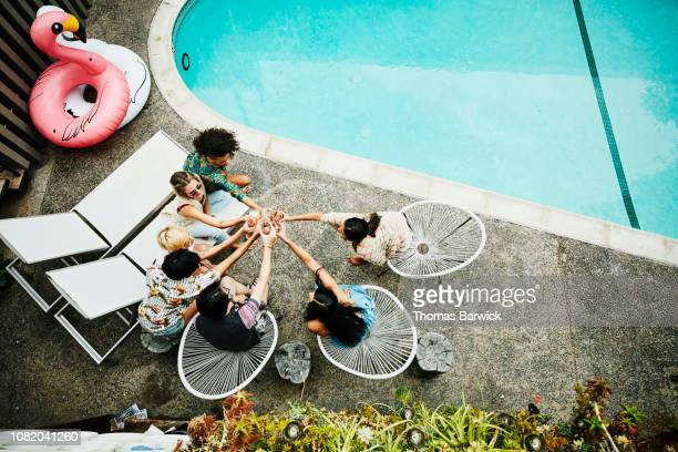 overhead view of friends toasting while sitting beside hotel pool - medium group of people stock pictures, royalty-free photos & images