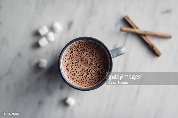 overhead view of frothy hot chocolate in mug with marshmallows and cinnamon on table - hot chocolate stock pictures, royalty-free photos & images
