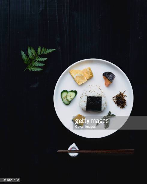 overhead view of garnished plate with chopsticks on black table - japanische kultur stock-fotos und bilder