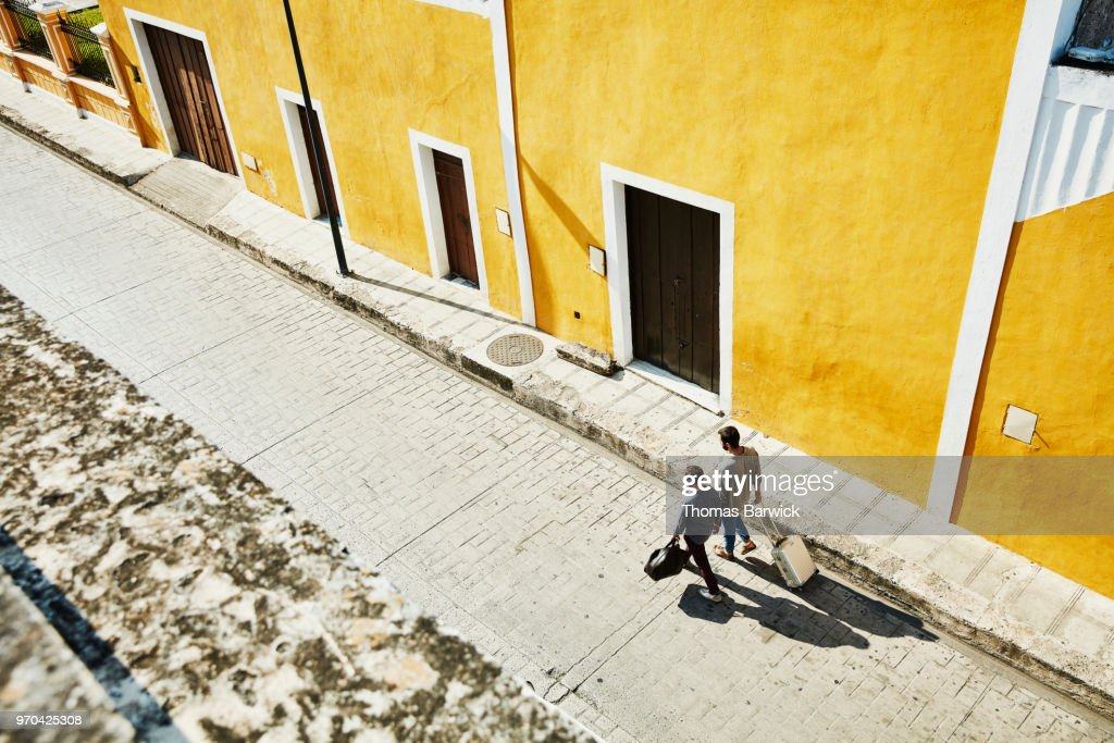 Overhead view of gay couple carrying luggage while walking down street in small town on vacation : Stock Photo