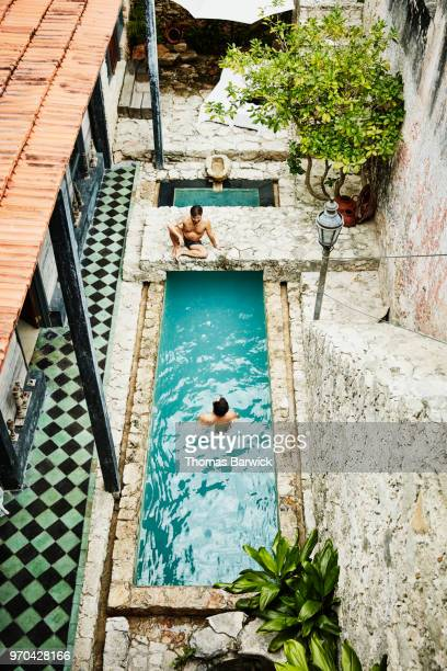 Overhead view of gay couple in courtyard pool of boutique hotel