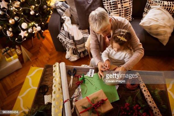 Overhead view of girl and grandmother packing gift at table during Christmas