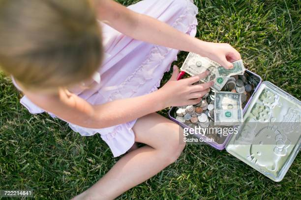 Overhead view of girl counting dollar bills on grass