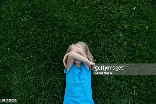 overhead view of girl covering face while lying on grassy field - shy stock pictures, royalty-free photos & images