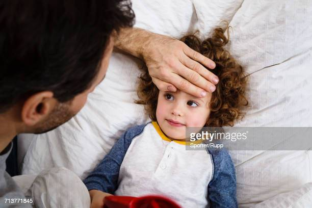 Overhead view of girl lying in bed with fathers hand on forehead