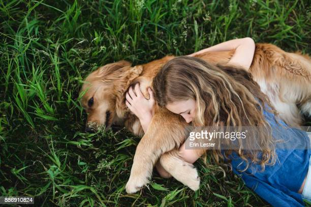 Overhead view of girl lying on grass hugging golden retriever dog