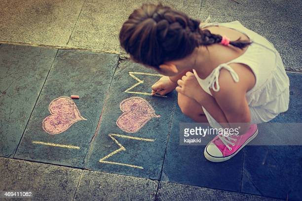 overhead view of girl using chalk to write i love mom  - chalk drawing stock pictures, royalty-free photos & images