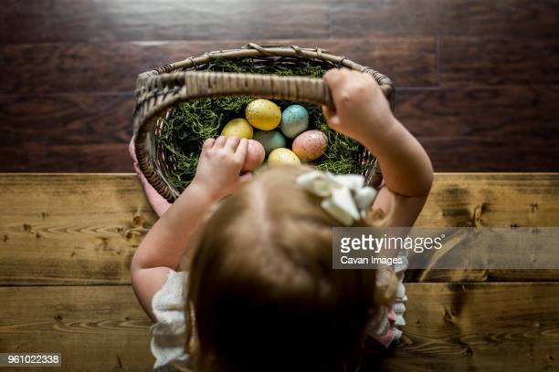 overhead view of girl with basket of easter eggs sitting on wooden table at home - easter basket stock pictures, royalty-free photos & images