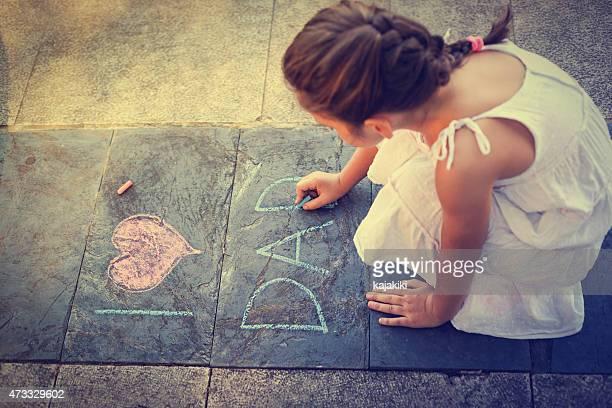 Overhead view of girl writing on the sidewalk