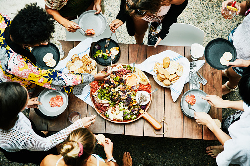 Overhead view of group of friends enjoying buffet of food during party - gettyimageskorea